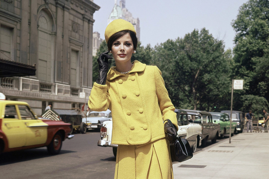 Mustard Yellow walking suit by Donald Brooks with jaunty matching beany is attention-getter on any avenue. Crisp knife pleated skirt offers plenty of stride room. Hip length double breasted jacket emphasizes bib effect with welt seaming. The costume is a part of the Townley collection for all and winter fashion suits shown June 20, 1962. (AP Photo/Bob Wands)