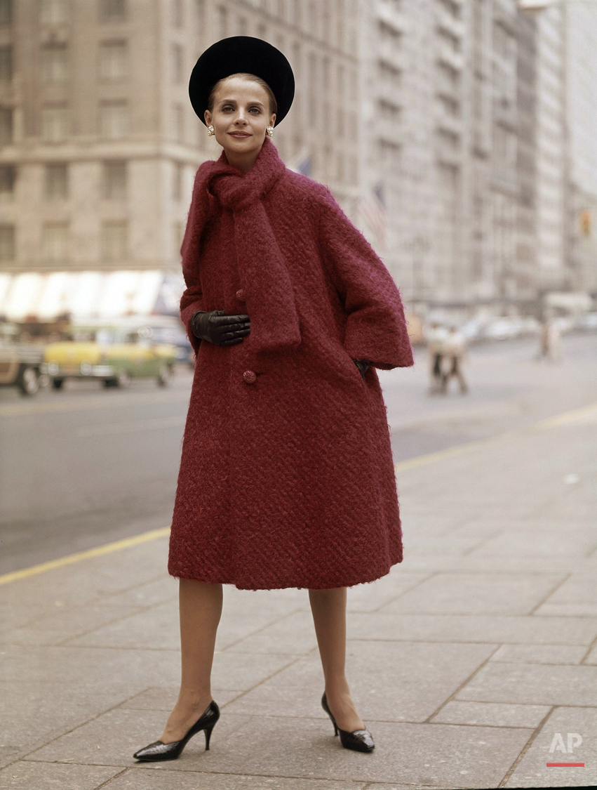 Red coat with brown gloves, black hat and shoes fashion coat in 1963. (AP Photo)