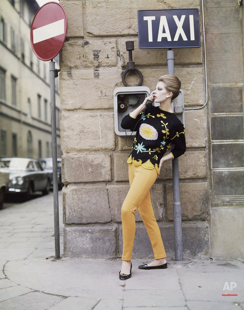 A sports outfit, consisting of a black woolen sweater with pink, orange and turquoise floral designs, and yellow-orange woolen pants, a creation by the Ilaria Gentucca fashion house of Lucca, presented at the Florence show of Italian spring and summer fashions, Jan. 18, 1965. (AP Photo)